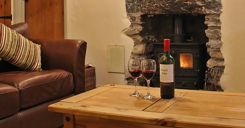 relax in holiday rental lounge with real woodburning stove fire